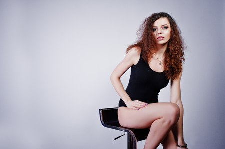 Brunette curly haired long legs girl in black swimsuit posed on chair at studio against white background.