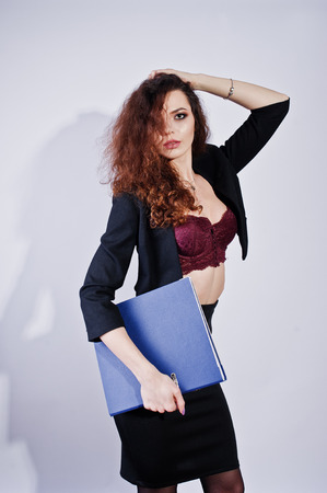 Brunette curly haired girl in black office jacket with skirt, on bra with folder of documentts at hands on studio against white background. Sexy businesswoman.
