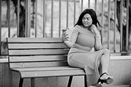 African american woman model xxl in orange dress looking on mobile phone. Stock Photo