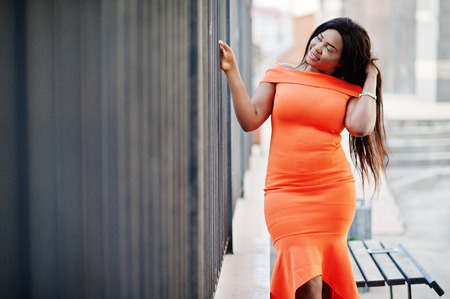 African american woman model xxl in orange dress. Stock Photo