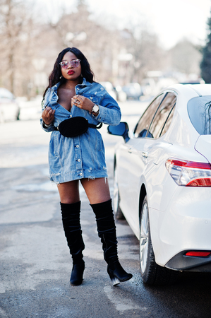 African american girl in jeans dress and sunglasses posed against white business car on streets of city. Black stylish model shoot.