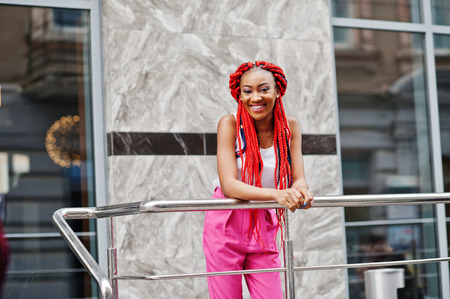 Fashionable african american girl at pink pants and red dreads posed outdoor.