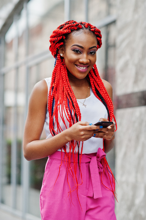 Fashionable african american girl at pink pants and red dreads posed outdoor with mobile phone.