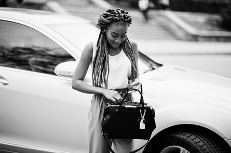 Fashionable african american business woman at pink pants and red dreads posed outdoor with bag against her luxury car.