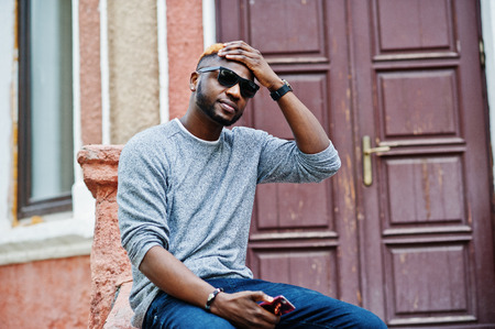 Stylish african american boy on gray sweater and black sunglasses posed on street. Fashionable black guy. 스톡 콘텐츠
