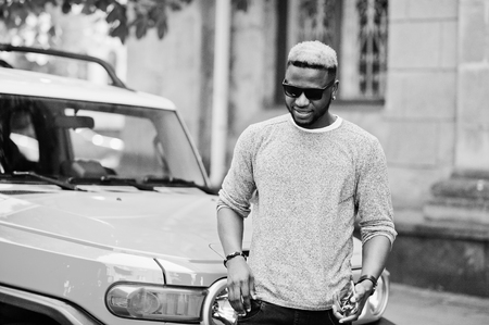 Stylish african american boy on gray sweater and black sunglasses posed on street against yellow car. Fashionable black business man.