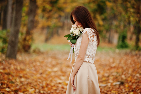 Amazingly girl bridesmaid in golden dress with bouquet at hands at autumn park. Stock Photo