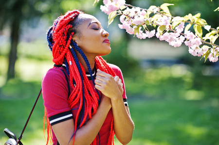 Cute and slim african american girl in red dress with dreadlocks posed outdoor in spring park. Stylish black model.