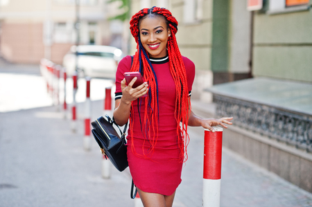 Cute and slim african american girl in red dress with dreadlocks and backpack posed outdoor and looking at mobile phone on street. Stylish black model. Stock Photo