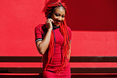 Cute and slim african american girl in red dress with dreadlocks posed outdoor against red wall. Stylish black model.