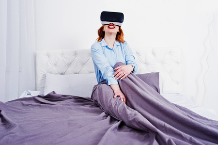 Red haired girl in bed with vr glasses at studio room.