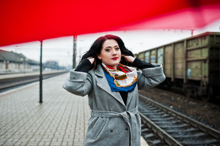 Brunette girl in gray coat with red umbrella in railway station.