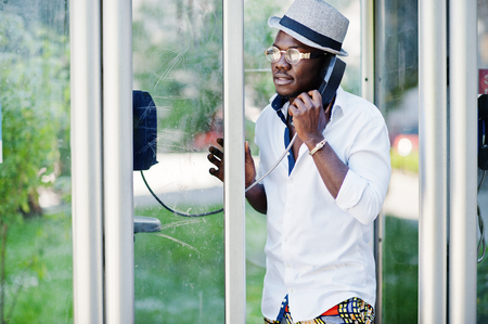 Stylish african american man in white shirt and colored pants with hat and glasses posed outdoor at telephone booth. Black fashionable model boy.