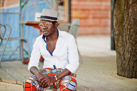 Stylish african american man in white shirt and colored pants with hat and glasses posed outdoor. Black fashionable model boy. Stock Photo