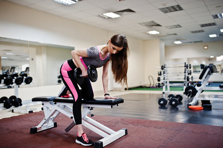 Young brunette sexy slim girl doing workout at gym. Sporty beautiful model doing exercises
