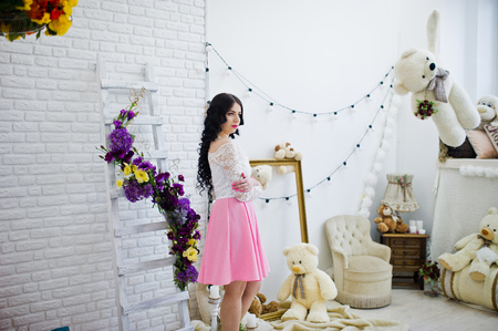 Young brunette girl in pink skirt and white blouse posed indoor against room with toys bear.