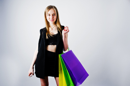 Girl model in black wear with colored shopping bags posed at studio on white background.  Stock Photo