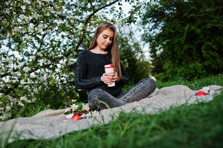 Young brunette girl at jeans sitting on plaid against spring blossom tree and holding tea thermos at hands.
