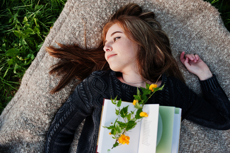 Young brunette girl lying on plaid with book.