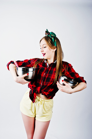 Young funny housewife in checkered shirt and yellow shorts pin up style with two saucepan isolated on white background. Stock Photo