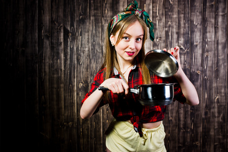 Young funny housewife in checkered shirt and yellow shorts pin up style with saucepan on wooden background.