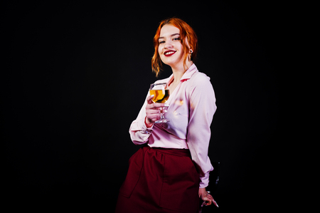 Gorgeous red haired girl in pink blouse and red skirt with glass of wine at hand isolated on black.