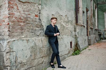 Young macho boy wear on blac stylish jacket smoking cigarette on streets.