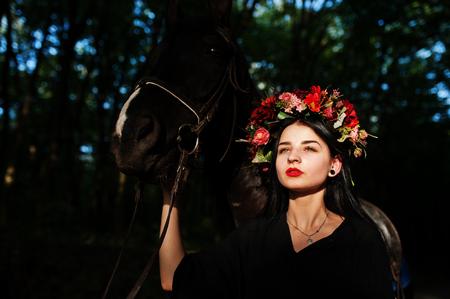Mystical girl in wreath wear in black with horse in wood.