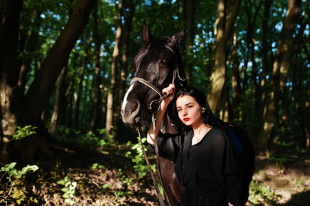 Mystical girl wear in black with horse in wood. Фото со стока