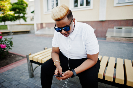 Stylish arabian muslim boy with originally hair and sunglasses posed on streets, sitting on bench and listening music from earphones of phone. Stock Photo