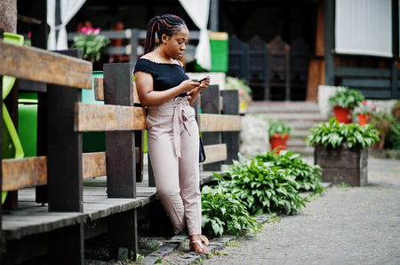 Stylish african american woman posed outdoor and using mobile phone. Stock Photo