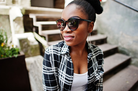 Hip hop african american girl on sunglasses and jeans shorts. Casual street fashion portrait of black woman.