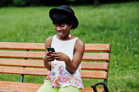 Amazing african american model woman in green pants and black hat posed on bench at park and texting on mobile phone.