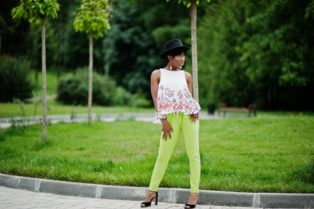 Amazing african american model woman in green pants and black hat posed at park. Stock Photo