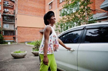 Amazing african american model woman in green pants and black hat posed near white door of car. Stock Photo
