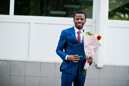 African american happy successful man at suit with diploma at graduation day.