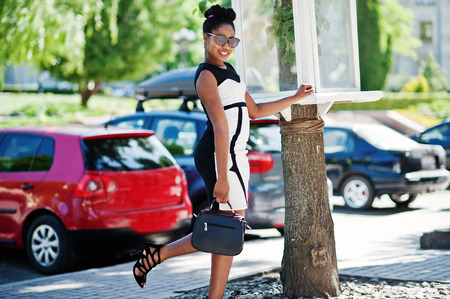 African american girl in sunglasses, black and white dress and handbag posed against cars parking. Stock Photo
