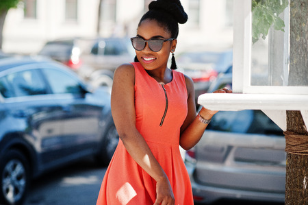 African american girl in sunglasses, peach dress and handbag posed against cars parking. Stock Photo