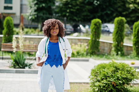 African american doctor female at lab coat with stethoscope outdoor.