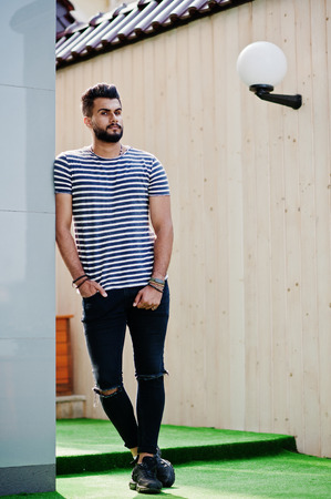 Handsome tall arabian beard man model at stripped shirt posed outdoor. Fashionable arab guy.