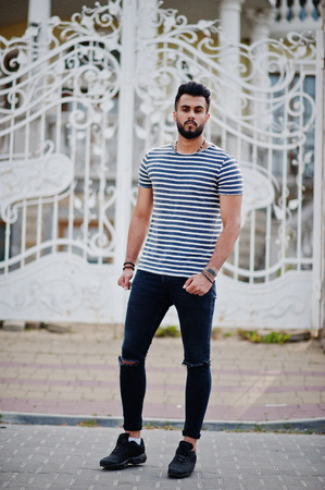 Handsome tall arabian beard man model at stripped shirt posed outdoor against royal iron gates. Fashionable arab guy.