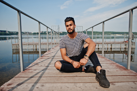 Handsome tall arabian beard man model at stripped shirt posed outdoor on pier of lake. Fashionable arab guy.