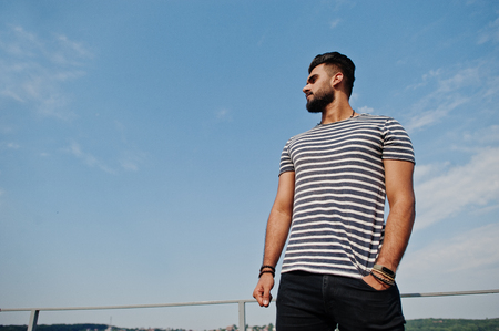 Handsome tall arabian beard man model at stripped shirt posed outdoor against sky. Fashionable arab guy.
