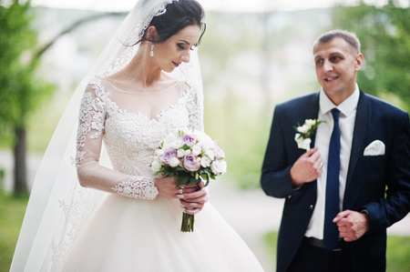 Gorgeous and happy newly married couple standing in green park on their wedding day.
