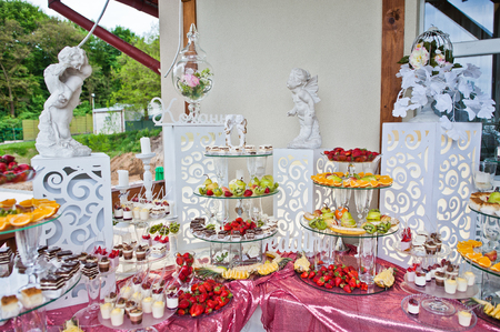 Catered table full of different snacks and fruits. Wedding banquet.