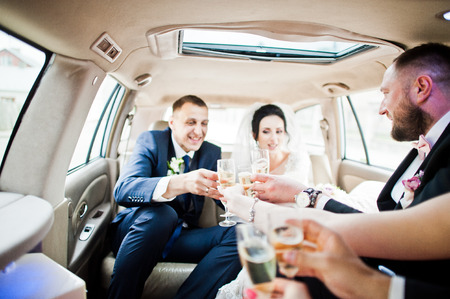 Groomsmen with bridesmaids and wedding couple drinking champagne in the car.