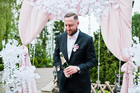 Groomsman opening up the bottle of champagne next to decorated wedding arch.