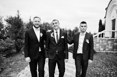 Groomsman and best man posing with groom next to the church. Black and white photo.