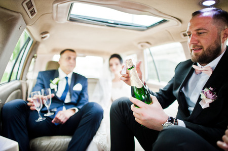 Groomsman opening the bottle and pouring champagni into glasses in the car. 免版税图像