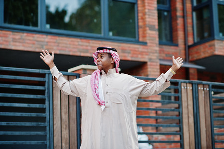 Middle Eastern arab man posed on street against modern building shows a surprise.